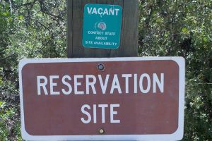 Sign says Reservation Site with green Vacant tag