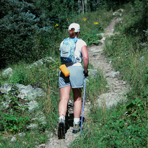 A woman hiker with her back to the camera walks up a mountain trail