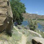 Trail runs between rocks and a lake