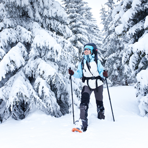 A person facing towards the camera wearing winter gear walks on snowshoes in a snow covered forest
