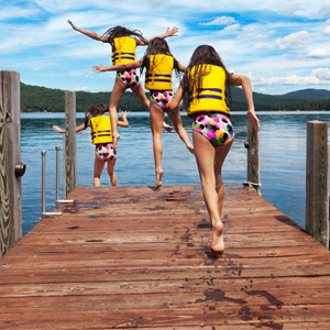 A girl wearing a yellow life jacket jumping off a dock. The girl is repeated four times as she runs and jumps to give the illusion of a time lapse photo